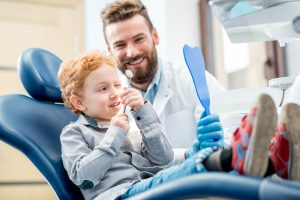 young boy with red hair sitting in dental chair excited as dentist holds a mirror up for him